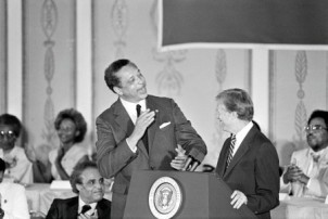 Leon Sullivan, local chairman of the Opportunities Industrialization Centers (L) leaps from his chair to congratulate President Carter on his